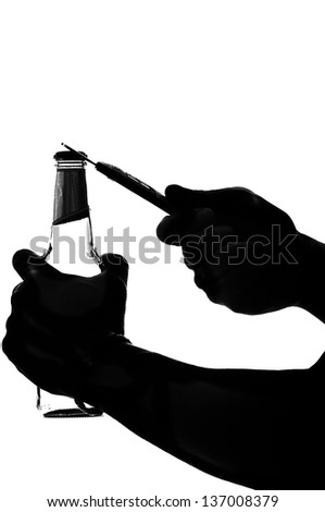 silhouette of a hand holding and opening beer bottle with metal opener