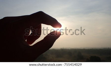 Silhouette of a hand picking sunlight in the morning Success, dream and belief concept - Shutterstock ID 755414029