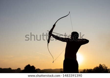 Silhouette of a handsome man with an ancient weapon bow and arrow on a background of sky and sunset #1483391390