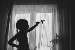 Silhouette of a happy child girl playing with a toy airplane in her room by the window. Dream to fly. Close the borders of air travel.