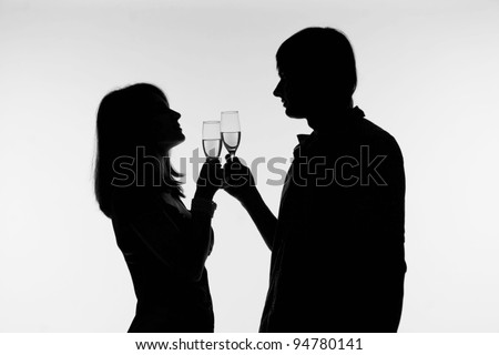 Silhouette of a happy couple with wine glasses as logo.