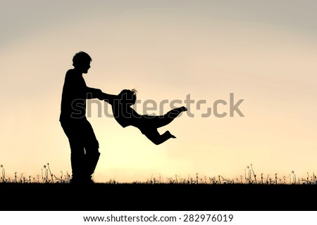 Silhouette of a happy father holding his little child\'s arms and spinning him in circles on a summer day.
