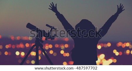 Photo of Silhouette of a happy girl with telescope and de-focused city lights. Elements of this image are only my work.