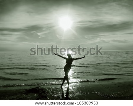 Silhouette of a happy young girl / woman in the water at sunset