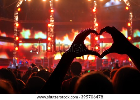Silhouette of a heart shaped hands and crowd of Audience is power of music concert
