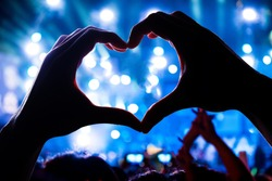 Silhouette of a heart shaped hands shadow of Audience Crowd people in music concert