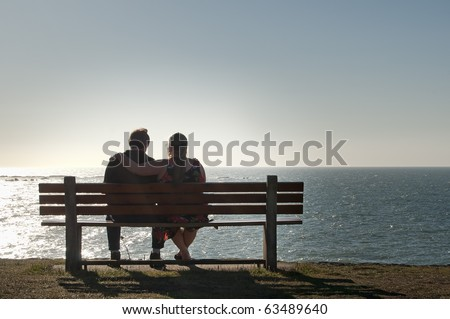 Silhouette of a heterosexual couple enjoying the afternoon on a calm and peaceful relaxing in front of the ocean view. Copyspace above with room for text.