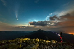 Silhouette of a hiker man with flashlight standing on mountain peak under starry sky lighting a beam og light on Neowise comet with light tail.