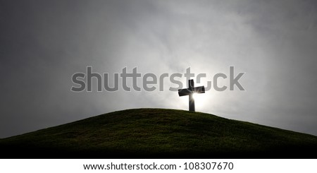 Silhouette of a holy christian crucifix illuminated by sunlight on top of a hill on a dramatic cloudy sky.