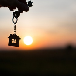 Silhouette of a house figure with a key, a pen with a keychain on the background of the sunset. They dream of a house, building, moving to a new house, mortgages, renting and buying real estate. Copy