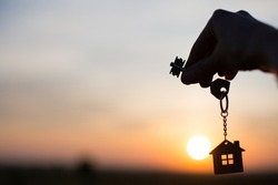 Silhouette of a house figure with a key, a pen with a keychain on the background of the sunset. They dream of a house, moving to a new house, mortgages, renting and buying real estate. Copy space