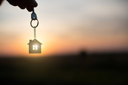 Silhouette of a house figure with a key,  keychain on the background of the sunset. They dream of a house, building, moving to a new house, mortgages, renting and buying real estate. Copy