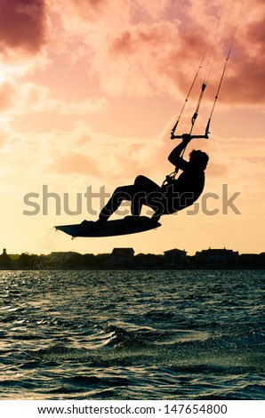 Silhouette of a kitesurfer flying above the water at sunset