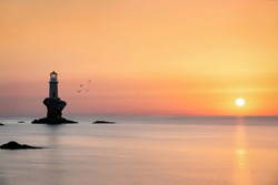 Silhouette of a lighthouse on a rock during a calm summer sunrise, Andros, Greece