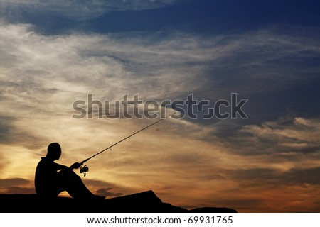 Silhouette of a lonely old fisherman waiting for his catch by a seaside on a surreal evening sunset.