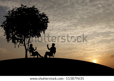 Silhouette of a loving couple drinking in an outdoor park against a glowing romantic sunset.