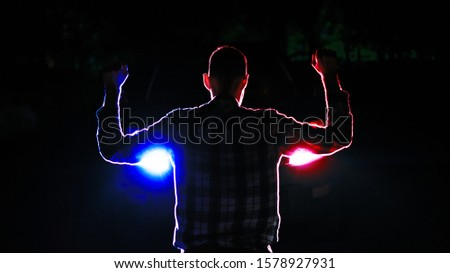 silhouette of  a male  criminal suspect with hands up during night pursuit in front of the police car headlights Stock photo ©