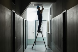 Silhouette Of A Male Electrician On Step Ladder Installing Light At Corridor