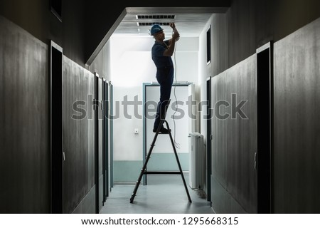 Silhouette Of A Male Electrician On Step Ladder Installing Light At Corridor Stock photo ©