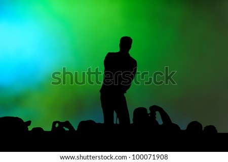 Silhouette of a male singer performing in front of a crowd with raised hands.