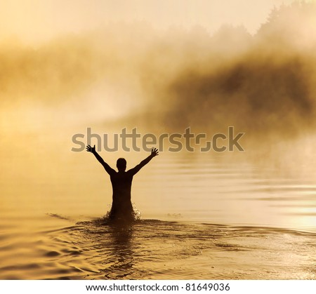 Silhouette of a male with raised arms in the water - stock photo