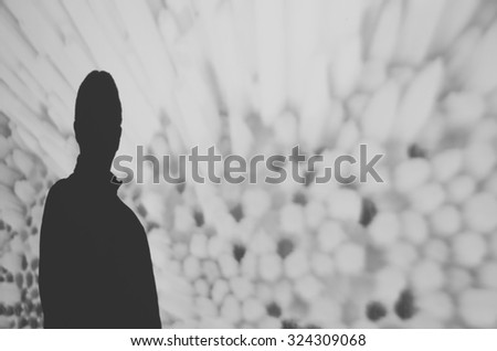 Silhouette of a man against a wall projected with floral patterns. Black and white image.  - Shutterstock ID 324309068