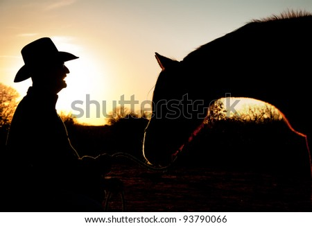 Silhouette of a man and his horse against sunset sky, with horse reaching towards man