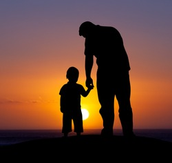 Silhouette of a man and his son with sunset background.