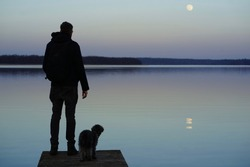 Silhouette of a man and its dog friend at a lake at sunset with moon and reflecting moonshine on water, concept and idea