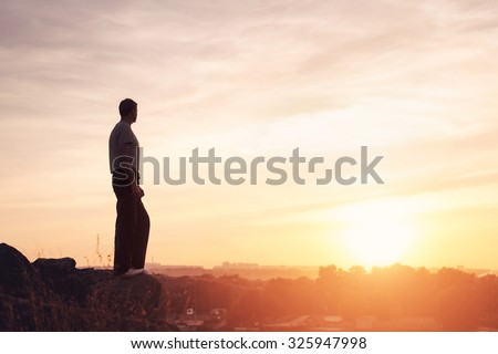 Silhouette of a man at the beautiful sunset on the mountain. Background #325947998