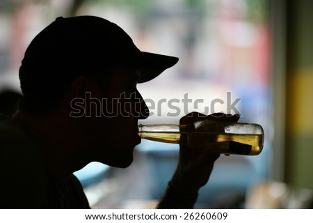 Silhouette of a man drinking beer. Close-up.