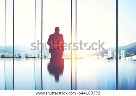 Silhouette of a man entrepreneur is pondering over the idea a business partnership which he got during a trip to China, while is standing in modern skyscraper interior against window with copy space Сток-фото ©