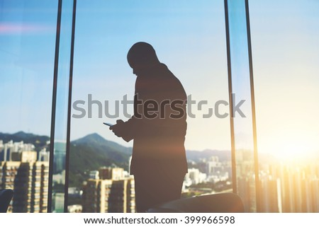 Silhouette of a man entrepreneur is typing text message on mobile phone to investor to consider again the question of funding, while is standing in office near big skyscraper window with city view