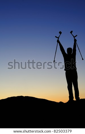 Silhouette of a man facing the dawn holding his crutches high above his head, greeting the sunrise.