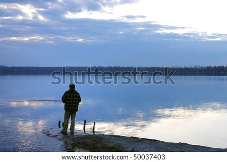 Silhouette of a man fishing in a sunset - stock photo