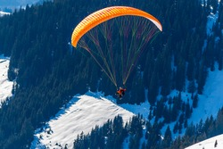 Silhouette of a man flying a hang glider in the mountains of Austria in the Zell am See area. Below the man is a snowy valley and forest.