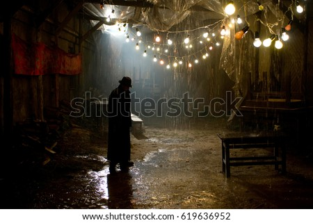 Silhouette of a man in a coat and hat in a dark alley on a rainy night #619636952