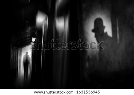 Silhouette of a man in a coat and hat in a dark alley on a rainy night. theme of violence and cruelty. blur effect Сток-фото ©