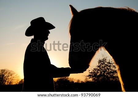 Silhouette of a man in a cowboy hat with his horse against sunset