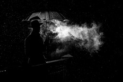 silhouette of a man in a hat under an umbrella at night in the rain in the city in the old crime Noir style