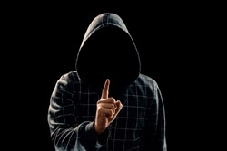 Silhouette of a man in a hood on a black background, his face is not visible, he lifts his finger up. The concept of a criminal, incognito, mystery, secrecy, anonymity.