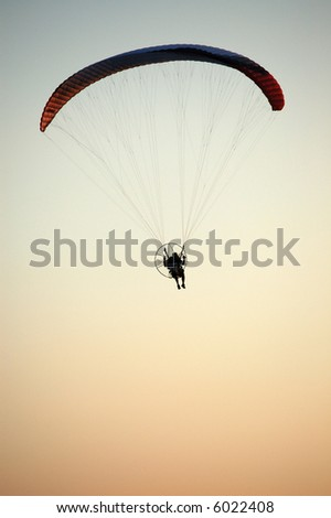 silhouette of a man in a motorized hang glider