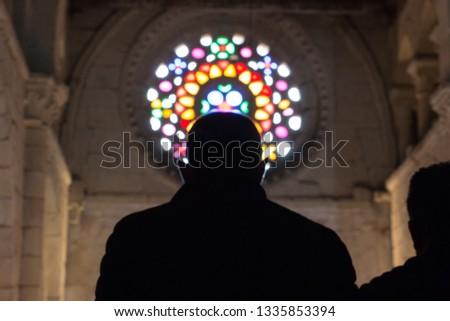 Silhouette of a man in backlight of a stained glass window praying in a 12th century church in Santa Mariña de Augas Santas, Allariz, Galicia, Spain. A Romanesque church.