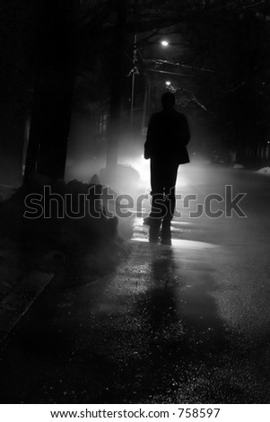 Silhouette of a man in front of a bright light outside on a cold winter night.