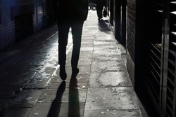 Silhouette of a man in the backlight walking down the street in the setting sun.