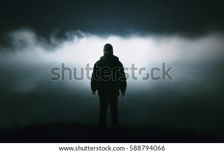 Stock Photo Silhouette of a man in the darkness. Night Photography. Dense fog over the river.