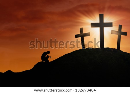 Silhouette of a man is praying for hope by the Cross under sunset background