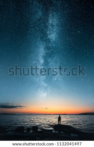 Silhouette of a man looking up on stars of the milky way with last light of sunset glows on the horizon #1132041497