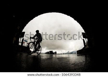 Silhouette of a man on a bicycle entering hochtor tunnel on the grossglockner mountain pass in a harsh rainy conditions.