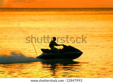 silhouette of a man on a waverunner